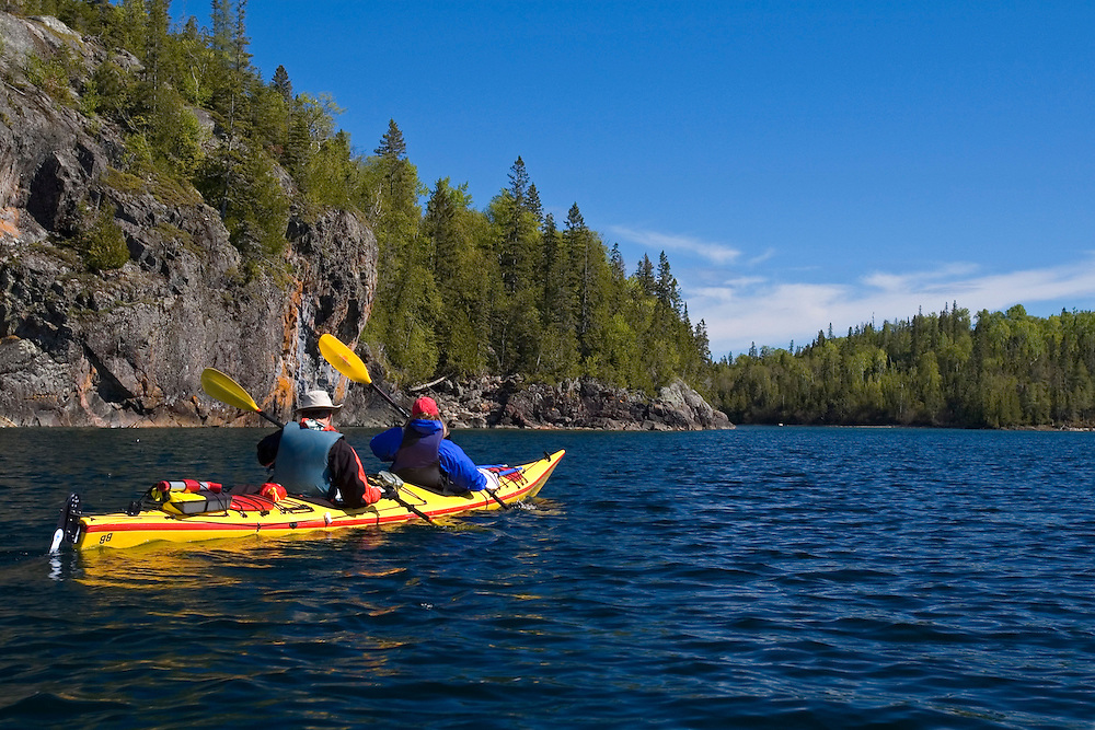 Sea kayakers explore the rugged shoreline of Chalfant Cove in Lake Superior Provincial Park near Wawa Ontario Canada.