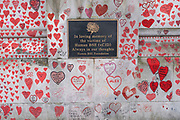 Memorial plaque for those who dies of BSE, vCJD aka Mad Cow Disease beaside red hearts painted in memory of people who have died of Covid-19 during the coronavirus pandemic at the National Covid Memorial Wall on 13th April 2021 in London, United Kingdom. The wall is  a place for people to come to reflect or to write messages or the names of lost loved ones. The wall represents a tribute to the approximately 150,000 British victims pandemic.