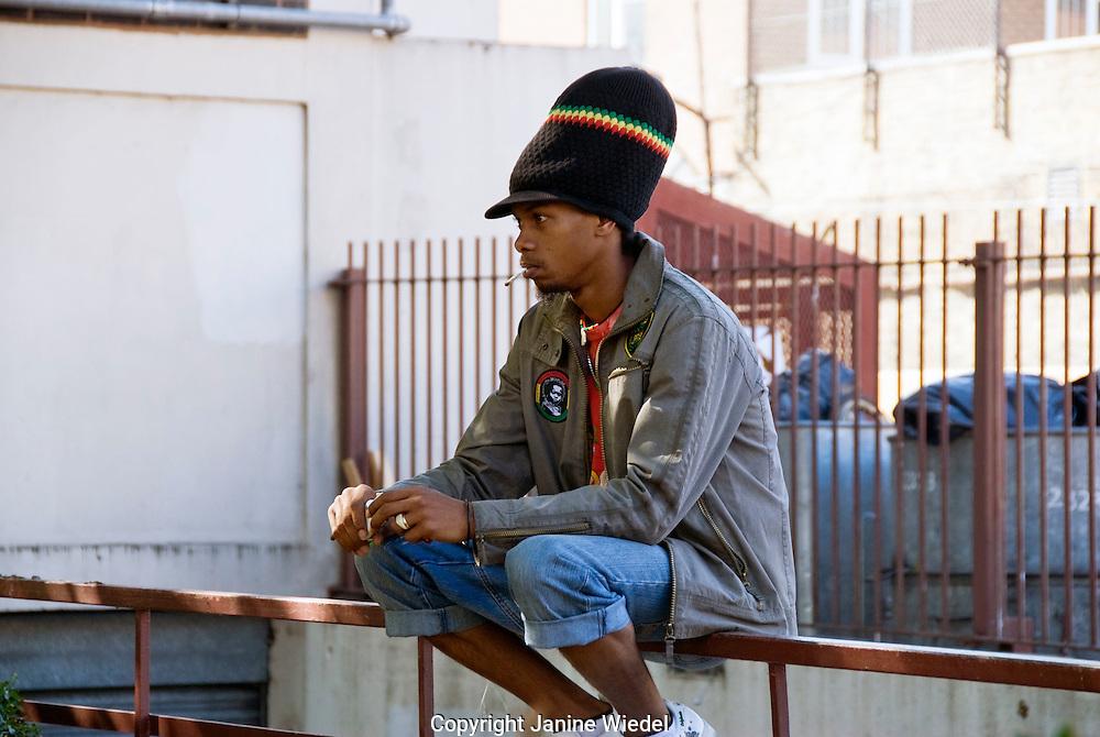 Rastafarian man sitting on railing