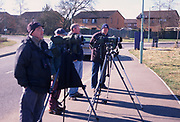 A794PD Birdwatchers stand in line with binoculars on tripods with housing in the background