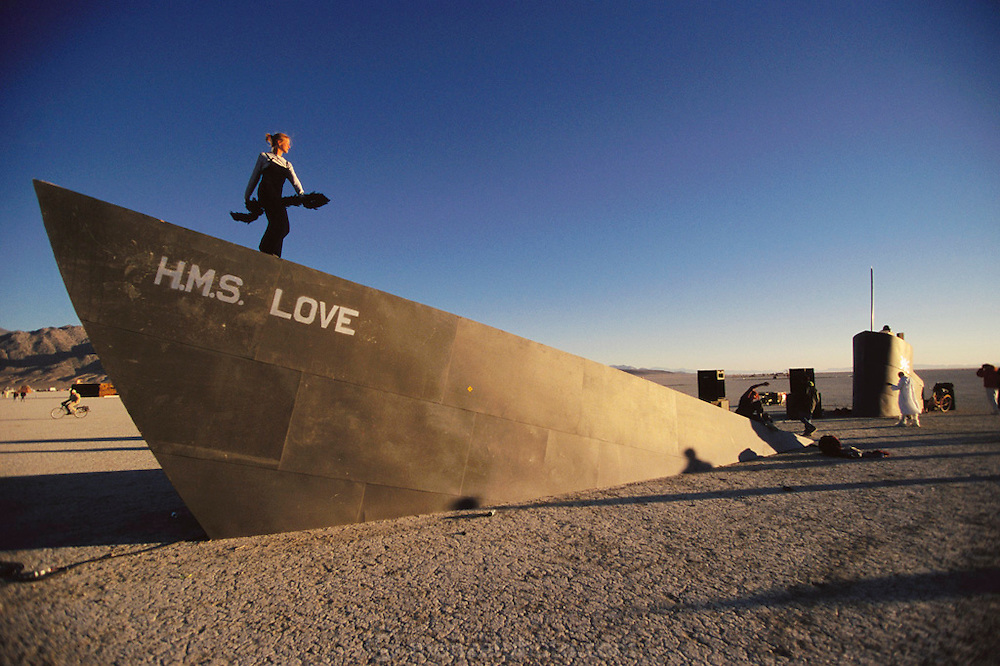 "A woman dances at dawn on the prow of the art installation ""HMS Love"", a sinking art ship in the desert. It is one of many art installations at Burning Man. Burning Man is a performance art festival known for art, drugs and sex. It takes place annually in the Black Rock Desert near Gerlach, Nevada, USA.."