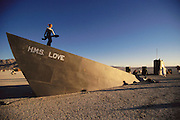 """A woman dances at dawn on the prow of the art installation """"HMS Love"""", a sinking art ship in the desert. It is one of many art installations at Burning Man. Burning Man is a performance art festival known for art, drugs and sex. It takes place annually in the Black Rock Desert near Gerlach, Nevada, USA.."""