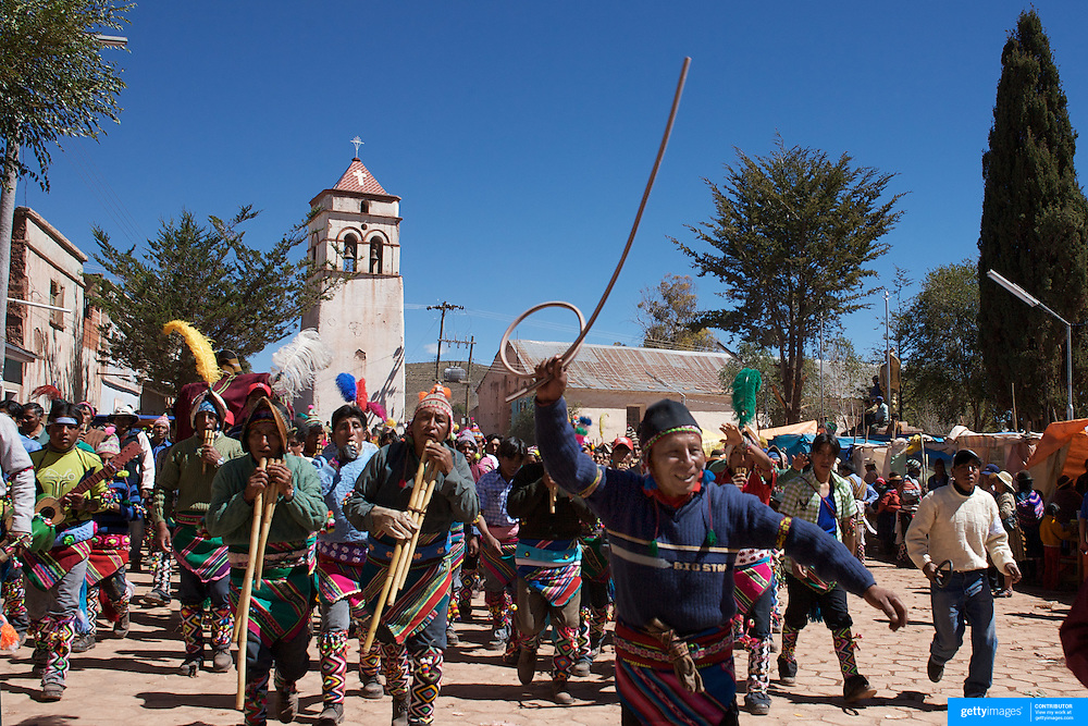Villagers arrive and run through the streets of Macha during the Tinku Festival. Macha, Bolivia, 4th May 2010, Photo Tim Clayton ..Each May, up to 3000 thousands indigenous Bolivian indians descend on the isolated mountainous village of Macha 75 miles north of Potosi in the Bolivian Andes. The 600 year old pre-hispanic Bolivia Festival of Tinku sees villagers from all over the region march into town to be pitted against each other in a toe to toe fist to fist combat.. They dance and sing in traditional costume and drink 96% proof alcohol along with chicha, a fermented beverage made from corn. Townspeople and sometimes the police oversee proceedings who often use tear gas to try and control the villages, whipped into a fighting frenzy by the dancing and alcohol, but as the fiesta goes on things often escalate beyond their control, with pitched battles between rival villages break out,  The blood spilt is an offering to the earth goddess - Pachamama - to ensure a good harvest for the coming year. Over the years dozens have died, yet the rite continues.