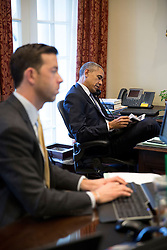 President Barack Obama talks on the phone with House Democratic Leader Nancy Pelosi, D-Calif., while sitting in the Outer Oval Office, March 26, 2015. Brian Mosteller, Director of Oval Office Operations, works at his desk. (Official White House Photo by Pete Souza)<br /> <br /> This official White House photograph is being made available only for publication by news organizations and/or for personal use printing by the subject(s) of the photograph. The photograph may not be manipulated in any way and may not be used in commercial or political materials, advertisements, emails, products, promotions that in any way suggests approval or endorsement of the President, the First Family, or the White House.