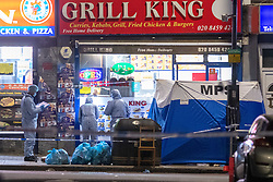 © Licensed to London News Pictures. 29/04/2021. London, UK. Forensic investigators look at a shop window next to a crime scene tent on High Road in Willesden following the fatal stabbing of a 40-year-old man. Police were called by London Ambulance Service at 17:11 BST to a report of a man suffering from stab wounds, despite the efforts of the emergency services the man was pronounced dead at the scene. Photo credit: Peter Manning/LNP