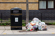 Bags of domestic rubbish seen next to a litter bin on a street in Tower Hamlets, east London, England on December 21, 2018.
