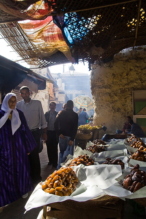 Shoppers gather around piles of large dried dates on sale at a street stall in a dark, busy street in Fes El-Bali, Morocco on October 31, 2007.