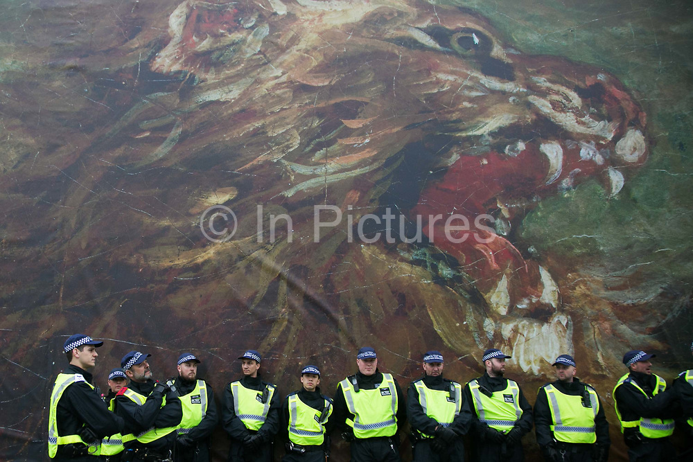 Peoples Assembly March for Health, Homes, Jobs and Education. End Austerity Now! march 16th April 2016 in London, United Kingdom. Police lined up against a painting of a lion in Trafalgar Square. 50.000 thousand plus turned out to protest against the Conservative Government and their austerity policies and against tax evasions revealed in the Panama Papers.
