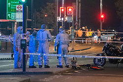 © Licensed to London News Pictures. 22/07/2021. London, UK. Forensic investigators stand next to a damaged bicycle at the scene as members of the victims family look on in the background following a fatal stabbing on Brixton Road, Brixton. Metropolitan Police Service (MPS) were called at 20:18BST on Wednesday 21 July to reports of an assault close to Brixton Underground Station. Despite efforts from police officers, paramedics from London Ambulance Service (LAS) and London's Air Ambulance the man was pronounced dead at the scene at the 20:45BST. Photo credit: Peter Manning/LNP