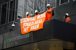 © Licensed to London News Pictures.02/02/2021, London,UK. Eco-activists protest on the top of a building's entrance while next to them bailiffs work to evict a group of eco-activists which is living in increasingly unstable tunnels beneath the Euston Square Gardens in central London.The eviction of HS2 Rebellion group from the square began five days ago and continues today.  Photo credit: Marcin Nowak/LNP