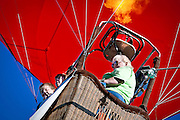 Levi Moore and Garret Powel peer over the edge of the Flying Goose hot air balloon as Carlotta Szabo, right, cranks up the liquid propane burner over Hayden City Park during Hayden Days Saturday evening.