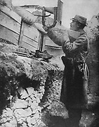 World War I 1914-1918: French soldier's improvised method of using his rifle with a periscope, enabling him to fire without putting his head above protective sandbags.  From 'Le Pays de France', Paris, 23 September 1915.