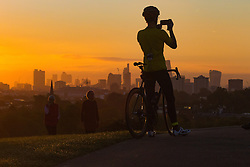 Primrose Hill, London, October 4th 2016. A cyclist photographs the sunrise from Primrose Hill as dawn breaks across London.