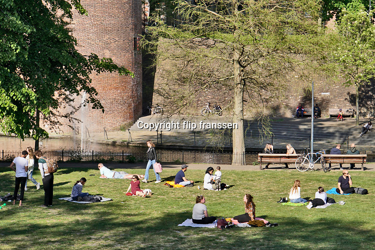 Nederland, Nijmegen, 25-4-2020 Mensen houden zich op in het Kronenburgerpark op deze mooie en warme lentedag . Ze proberen anderhalve meter afstand te houden vanwege de coronadreiging . De politie houdt regelmatig extra controle door met een auto door het park te gaan . surveillance, surveilleren . Foto: Flip Franssen