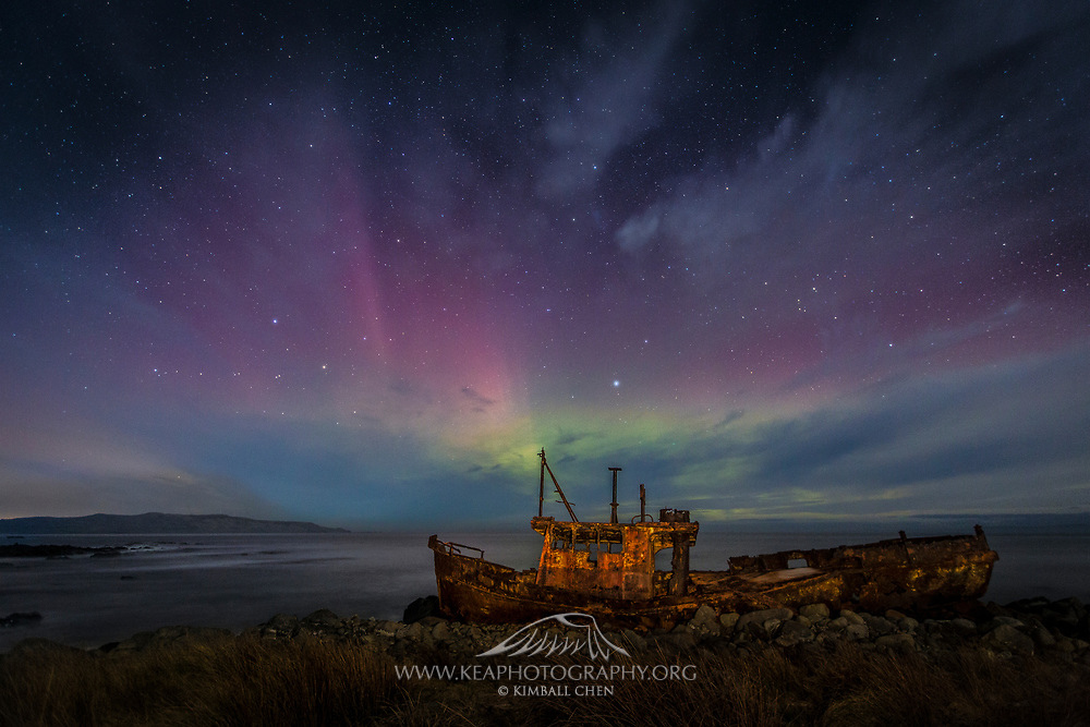 The Aurora Australis flickers above the rusted frame of a ship, in Southland, New Zealand. Not as bad as the rest of the country, but it was a chilly -2 degrees Celsius out last night (23rd of June 2015), with a bit of wind along the coast. Not a robust aurora display, but the subtle beams breaking behind the streaming clouds made for a better artistic result.