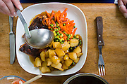 "Sunday dinner of baked chicken, potatoes, and frozen veggies prepared by Jill McTighe at her home in Willesden, London, United Kingdom.  (From the book What I Eat: Around the World in 80 Diets.) The caloric value of her day's worth of food on a ""bingeing"" day in the month of September was 12300 kcals. The calorie total is not a daily caloric average.  Jill is 31 years old; 5 feet, 5 inches tall;  and 230 pounds. Honest about her food addiction replacing a drug habit, Jill joked about being a chocoholic as she enthusiastically downed a piece of chocolate cake at the end of the photo session. Her weight has yo-yoed over the years and at the time of the picture she was near her heaviest; walking her children to school every day was the sole reason she didn't weigh more. She says this photo experience was a catalyst for beginning a healthier diet for herself and her family. ?Do I cook? Yes, but not cakes. I roast. Nothing ever, ever is fat-fried!?  Jill herself is MODEL RELEASED. [Use of Jill McTighe images must be used contextually only and use cleared with Peter Menzel Photography on a case by case basis.]"
