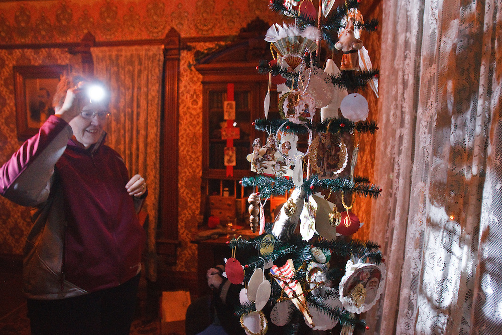 Jean Seely of Grand Island uses a flashlight to take a closer look at a late 19th century goose feather Christmas tree inside the Melisen House at the Stuhr Meseum during Christmas Past and Present Saturday night. Trees like this one could be hand made by first dying goose feathers, cutting them, and then wrapping them around sturdy wire to create the branches.  (Independent/Matt Dixon)