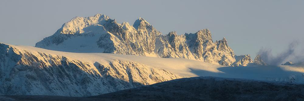 Montain with golden sunlight and snow. Blue clear sky   Fjell med gyllent sollys og snø. Blå klar himmel.