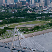 Vertical aerial photo of the Christopher S Bond Bridge with the Kansas City MO skyline in background.