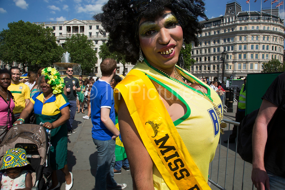 London, UK. Thursday 12th June 2014. A grotesque Miss Brazil drag beauty queen with wig and buck teeth and giant fake breasts. Brazilians gather for the Brazil Day celebrations in Trafalgar Sq. A gathering to celebrate the beginning of the Brazil 2014 FIFA World Cup. Revellers sing and dance and play football games and all in the yellow green and blue of the Brazilian flag.