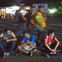 Migrants walking before dawn from Huixtla to Pijijiapan. Thousands of people have fled Honduras and to walk together in a caravan towards the US border.