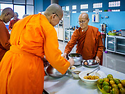 13 JANUARY 2019 - NAKHON PATHOM, THAILAND:  Female monks at Wat Songdhammakalyani get breakfast after their morning alms rounds. The Sangha Supreme Council, Thailand's governing body of Buddhist monks, bans the ordination of female monks, but hundreds of Thai women have gone abroad, mostly to Sri Lanka and India, to be ordained. There are about 270 women monks in Thailand and about 250,000 male monks. There are 7 monks and 6 novices at Wat Songdhammakalyani in Nakhon Pathom. It was the first temple in Thailand to have female monks. The temple opened 60 years ago and has always been a temple of women monks. Women can be ordained as novices in Thailand, but to be ordained as a full monk would require the participation of 10 female monks and 10 male monks, and male monks in Thailand are barred from participating in women's ordination ceremonies.     PHOTO BY JACK KURTZ
