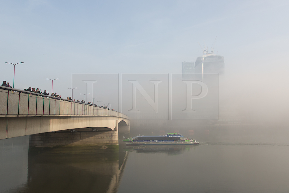 © Licensed to London News Pictures. 13/03/2014. London, UK. Thick fog begins to lift in morning sunlight over London Bridge on the River Thames and the 'Walkie Talkie' skyscraper in London on 13th March 2014. Photo credit : Vickie Flores/LNP