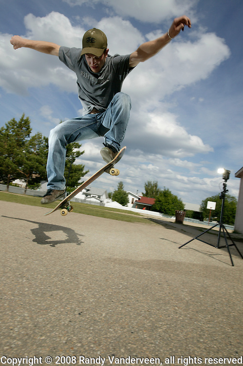 © 2008 Randy Vanderveen, all rights reserved.Grande Prairie, Alberta.Kirk Siemens performs some tricks for the camera on his skateboard in a school playground on a sunny late spring afternoon in Grande Prairie, Alberta.