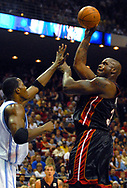 Miami Heat center Shaquille O'Neal, right, puts up a shot over Orlando Magic center Dwight Howard during the first half of their basketball game in Orlando, Florida.