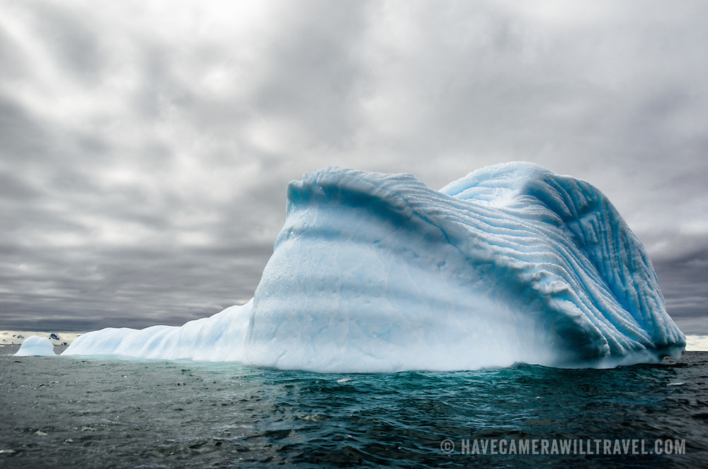 A iceverg floats in Antarctic waters, with deeply etched grooves  forming pattterns in the side created by trapped compressed air escaping as the iceberg slowly melts.