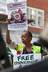 London, UK. 29 July, 2019. Sara Callaway of Women of Colour in the Global Women's Strike joins activists from Reclaim the Power, All African Women's Group, Docs Not Cops, Lesbians and Gays Support the Migrants and other groups at a protest outside the Home Office to demand an end to the Government's 'hostile environment' policies.