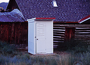 Pristine white outhouse adjacent to log cabin in Twin Lakes, Colorado.