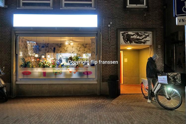 Nederland, Nijmegen, 24-12-2020 Lockdown in Nederland tijdens de dag voor kerstmis. De niet essentiele winkels zijn dicht. Kerstversiering hangt in de straten. Het is stil en leeg in de stad vlak voor kerstavond. Restaurants proberen nog  wat omzet te halen uit take away maaltijden en het bezorgen aan huis met een fietskoerier .Foto:Flip Franssen