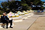 Man resting on seats in Parc Guell, Barcelona, Catalonia, Spain. A public park design by famed Catalan architect Antoni Gaudi featuring gardens and architectural curiosities.