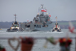 """© Licensed to London News Pictures. 09/01/2017. Portsmouth, UK.  Tugs escort the Polish Navy's youngest ship, ORP Kontradmiral Xawery Czernicki, """"Czernicki"""", sails into Portsmouth Harbour this morning, 9th January 2017. The multi-role support ship is visiting Portsmouth before deploying on a 6-month mission to join Standing NATO Maritime Group 2 (SNMG2) in the Mediterranean Sea. Photo credit: Rob Arnold/LNP"""