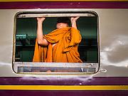 22 OCTOBER 2014 - BANGKOK, THAILAND: A Buddhist monk opens the window on a train in Hua Lamphong Train Station in Bangkok.        PHOTO BY JACK KURTZ