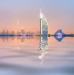 evening skyline view across sea towards Burj al Arab Hotel and city in Dubai United Arab Emirates