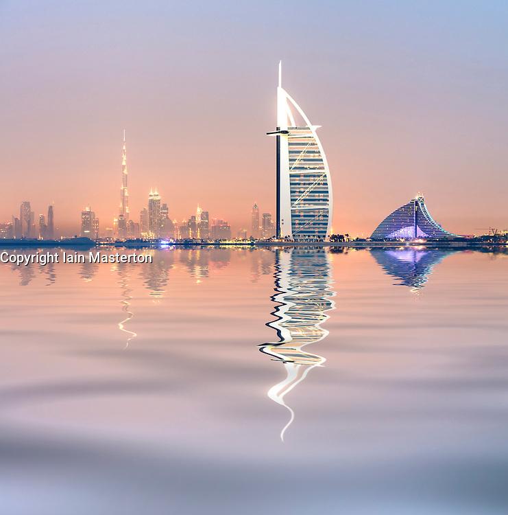 evening skyline view across sea towards Burj al Arab Hotel and city in Dubai United Arab Emirates