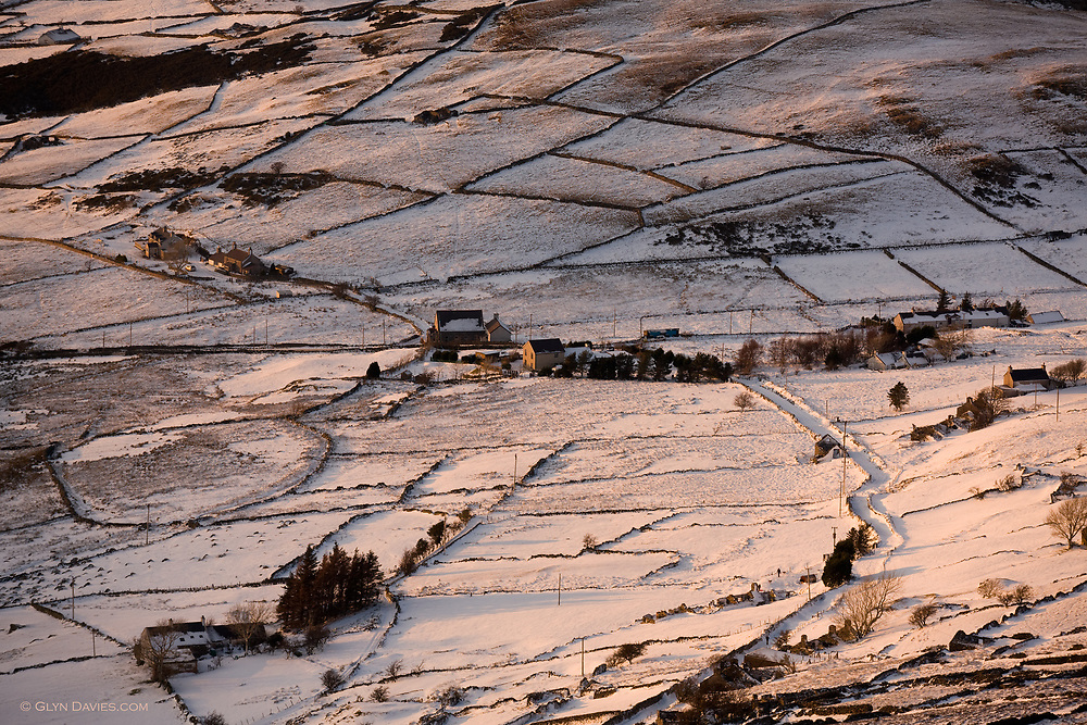A few houses in a snow covered winter rural landscape of trees and fields, high above the town of Deiniolen, Gwynedd, North Wales, in warm evening sunlight