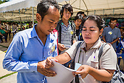 """17 JULY 2014 - BANGKOK, THAILAND:  A Thai immigration worker (right) helps an undocumented Cambodian man apply for a work permit at the temporary """"one stop service center"""" in the Bangkok Youth Center in central Bangkok. Thai immigration officials have opened several temporary """"one stop service centers"""" in Bangkok to register undocumented immigrants and issue them temporary ID cards and work permits. The temporary centers will be open until August 14.   PHOTO BY JACK KURTZ"""