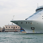 VENICE, ITALY - AUGUST 11: A large cruise ship sails in front of St Mark's Square on August 11, 2011 in Venice, Italy. Italian heritage group Italia Nostra warned  that Venice is facing an irreversible environmental catastrophe unless visitor numbers are capped. The acceptable maximum number of tourists for Venice is 33,000. In 2011 the average number of visitors to the city daily is 60,000 that is too high for such a fragile city and is causing the gradual destruction of the lagoon ecosystem.
