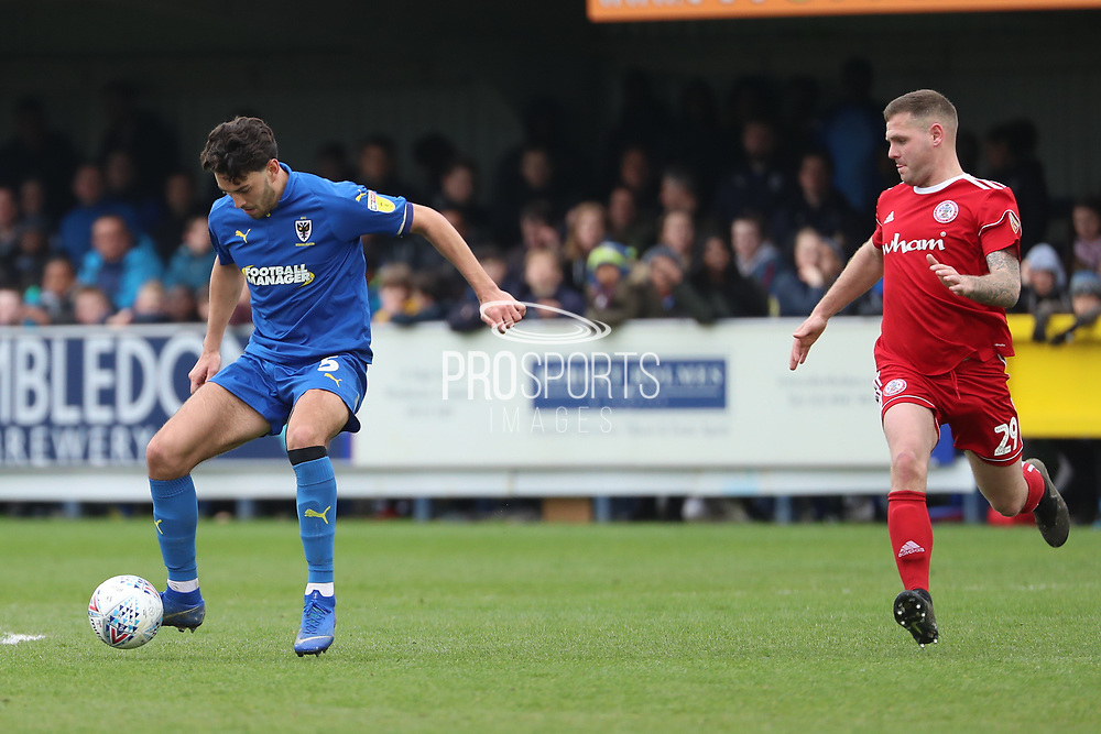 AFC Wimbledon defender Will Nightingale (5) dribbling and about to take on Accrington Stanley attacker Billy Kee (29) during the EFL Sky Bet League 1 match between AFC Wimbledon and Accrington Stanley at the Cherry Red Records Stadium, Kingston, England on 6 April 2019.