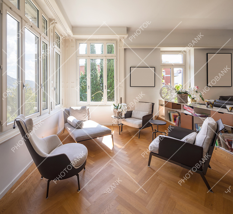 Living room area for conversation with armchairs and chaise longue. Bright windows overlooking the nature. Nobody inside