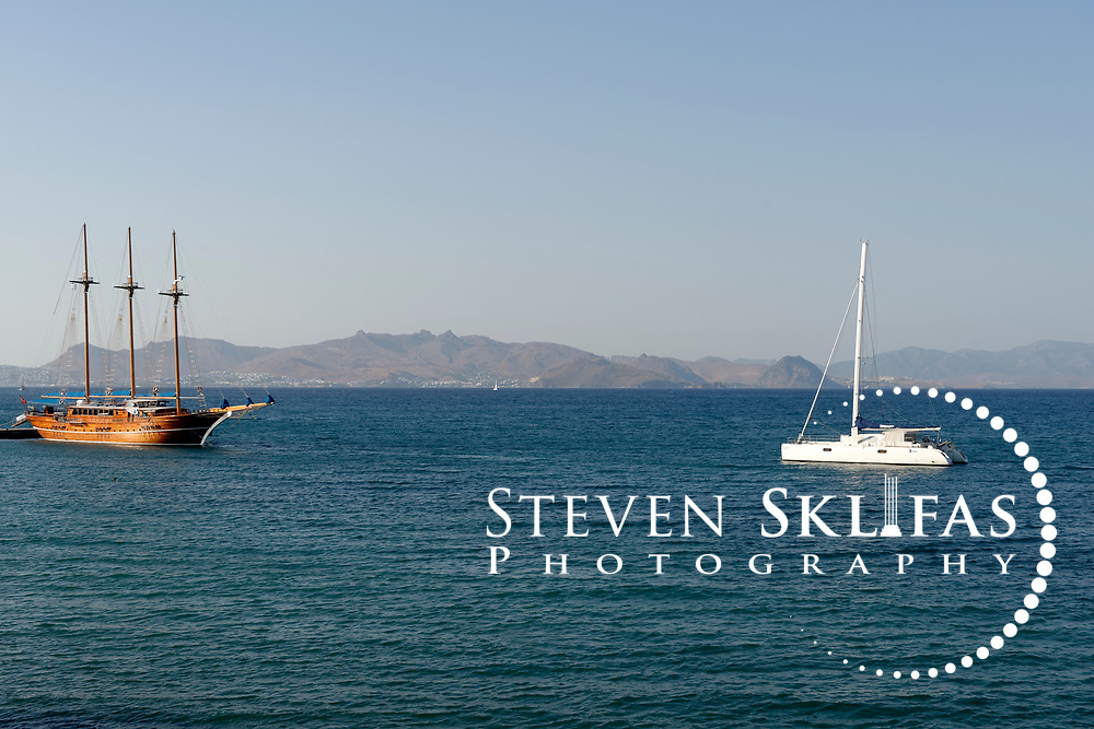Boats sailing in in the waters around Kos town, the capital of the Greek island of Kos. In the background is the coast of Asia Minor (Turkey). Kos is part of the Dodecanese island group and birthplace of the ancient physician and father of medicine, Hippocrates.