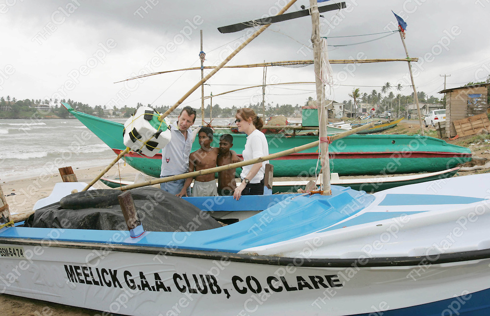 While travelling through Sri Lanka a week ago local photographer Liam Burke from Parteen, Co. Clare and Siobhan Walsh, Executive Director of Concern and a native of Fedamore, Co. Limerick came across this fishing boat donated by Meelick GAA Club.  With them are Daunk Kamura(14) a grandson of the boats newe owner and his friend  Nuvin Jusinda(14).  Over 34,000 Sri Lankans lost their lives and another 4,000 are still missing believed dead following the Tsunami which hit the country on December 26th last.  Concern Worldwide is helping survivors re-build their lives following the disaster.<br /> Picture: Press 22