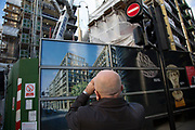 Bald man with his hair cut very short takes a photo of a building under construction, unawares that the crane on the other side of the hoarding says 'Baldwins'. London, UK.