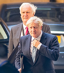 © Licensed to London News Pictures. 25/07/2019. London, UK. Prime Minister Boris Johnson straightens his tie as he arrives at Parliament with Sir Edward Lister his Chief of staff. The Conservative Party has elected Boris Johnson as their new leader and Prime Minister, following Theresa May's resignation. Photo credit: Peter Macdiarmid/LNP