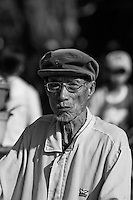 Old man wearing a cap and glasses on the streets of Hoi An.