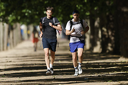 © Licensed to London News Pictures. 14/06/2021. London, UK. Runners jog along The Mall in central London. Another day of high temperatures is expected in the UK. Photo credit: Peter Macdiarmid/LNP