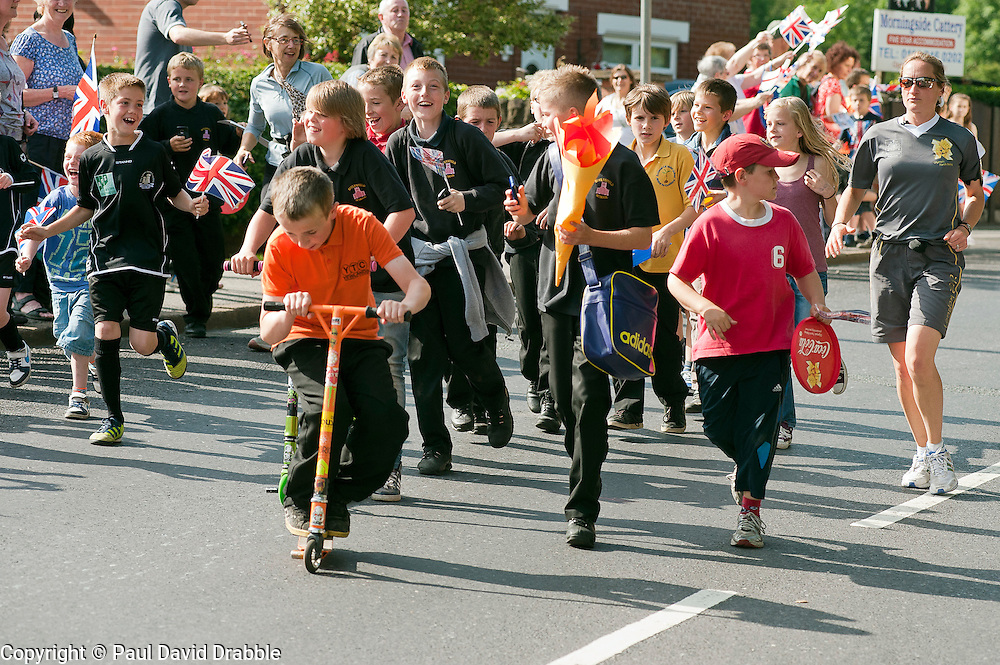The Olympic Torch relay reaches Sheffield on day 38 coverage from the Chapeltown - Ecclesfield - Parson Cross section of the Journey.<br /> Local children from Ecclesfield School run along side the Torch Bearer down Chapeltown Road<br /> 25 June 2012.Image © Paul David Drabble